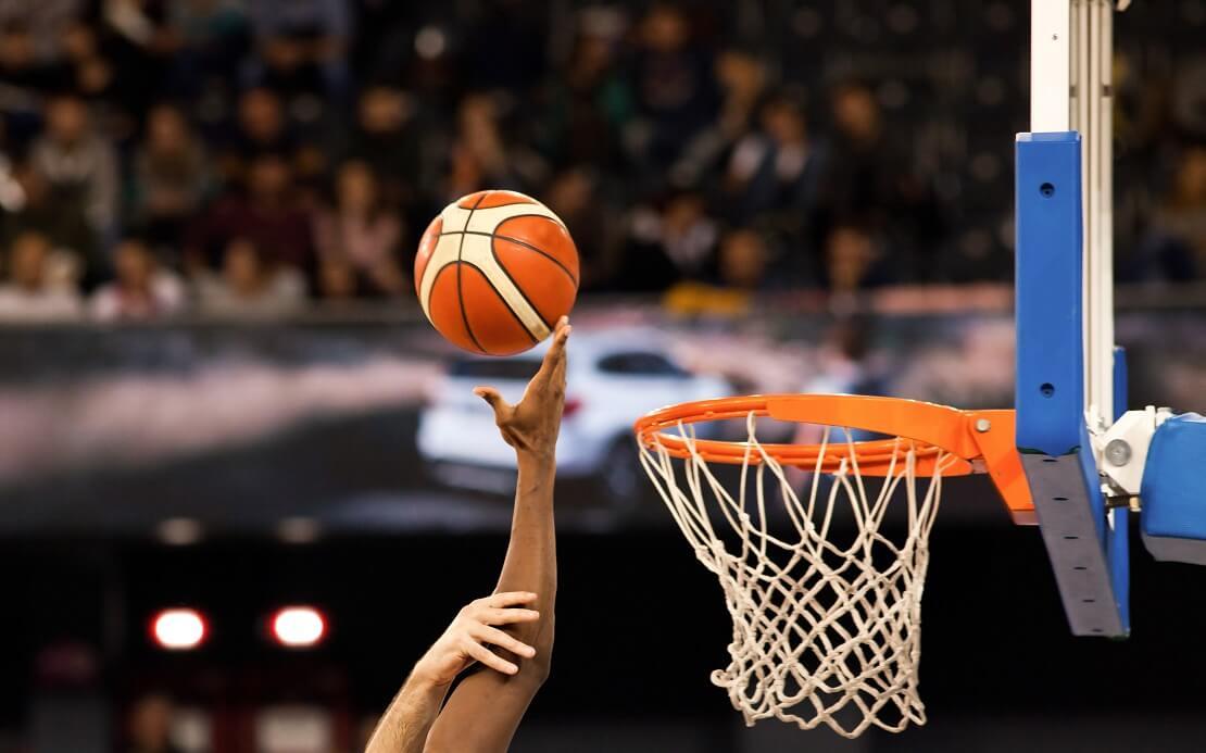 Eine Hand versenkt den Ball im Korb