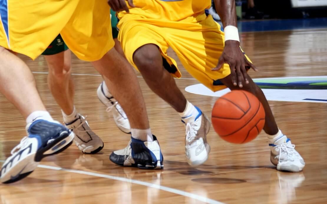 Ein Spieler dribbelt den Ball, sein Mitspieler stellt den Block