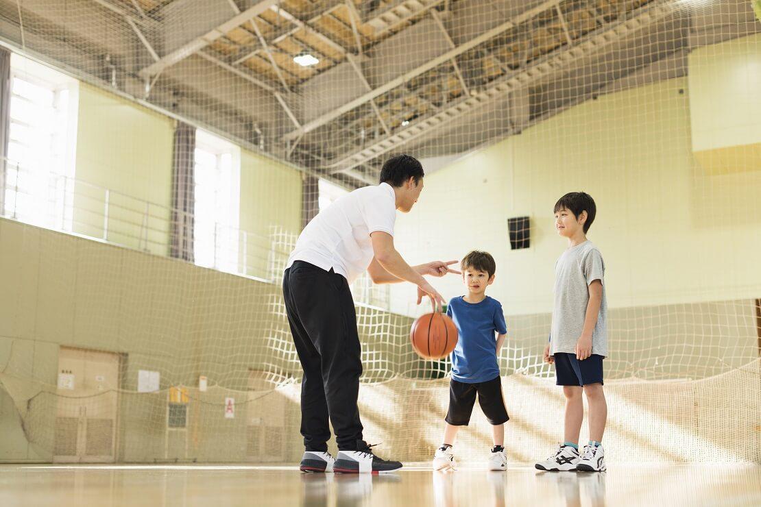 Basketballcoach steht mit einem Ball vor zwei Kindern