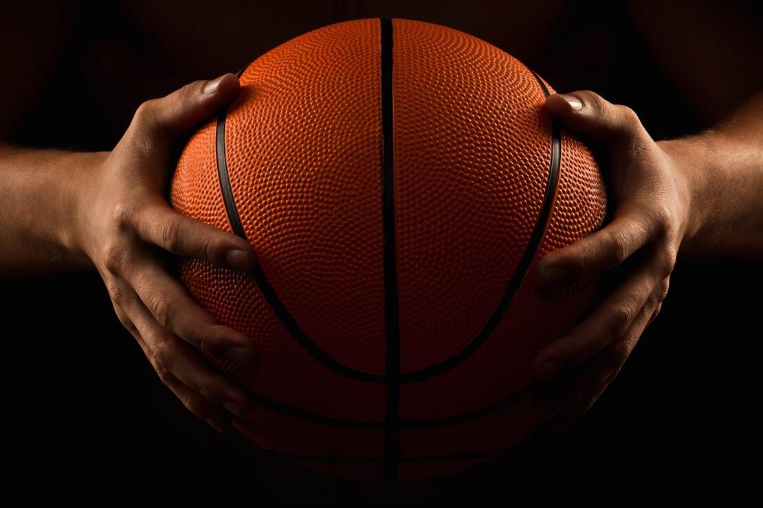 Basketballer haelt den Ball in den Haenden