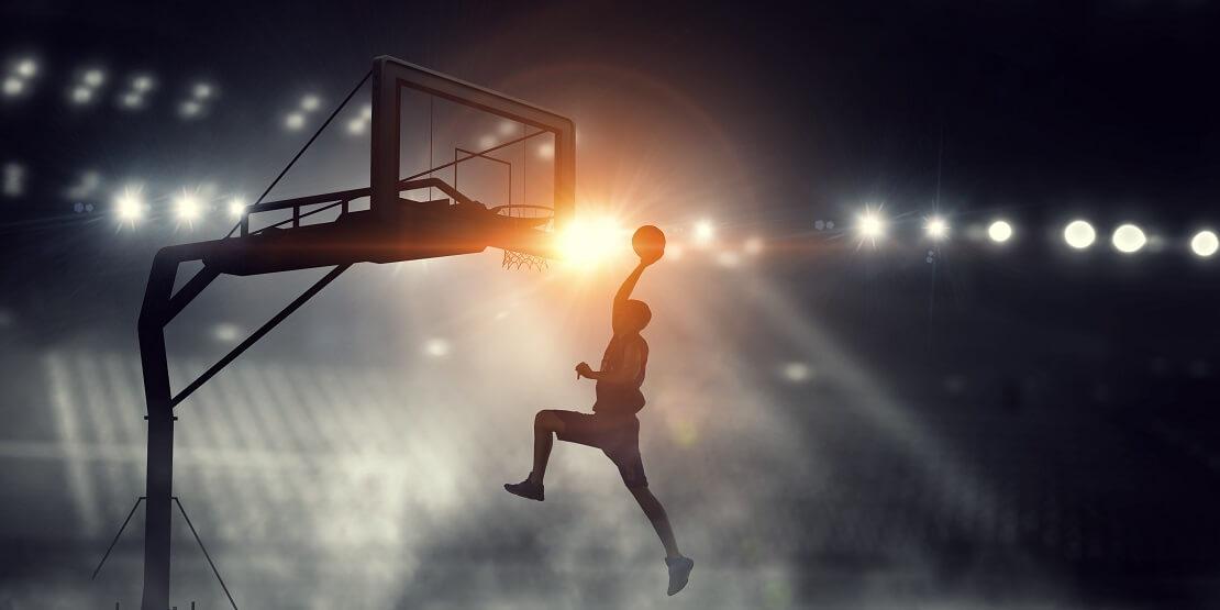 Ein Basketballer beim Dunking vor leeren Raengen