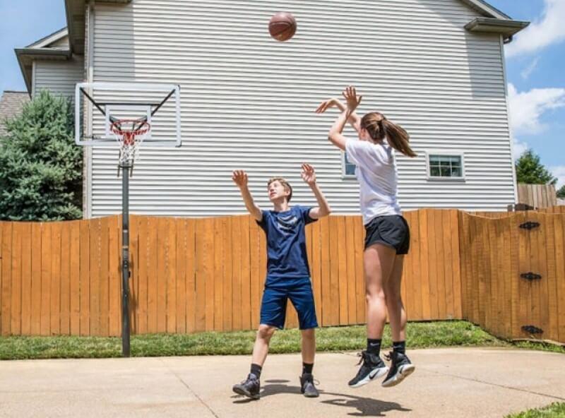 Ein Mädchen wirft auf einen heimischen Basketballkorb, ein Junge versucht zu blocken