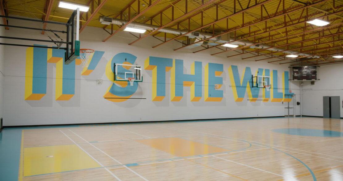 """Eine leere Basketballhalle, auf der Wand steht """"it's the will"""""""