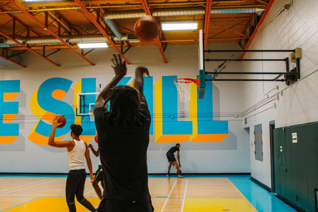 Ein Basketballer mit Dreadlocks wirft einen Ball auf einen Korb