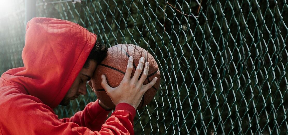 Basketballer lehnt am Zaun